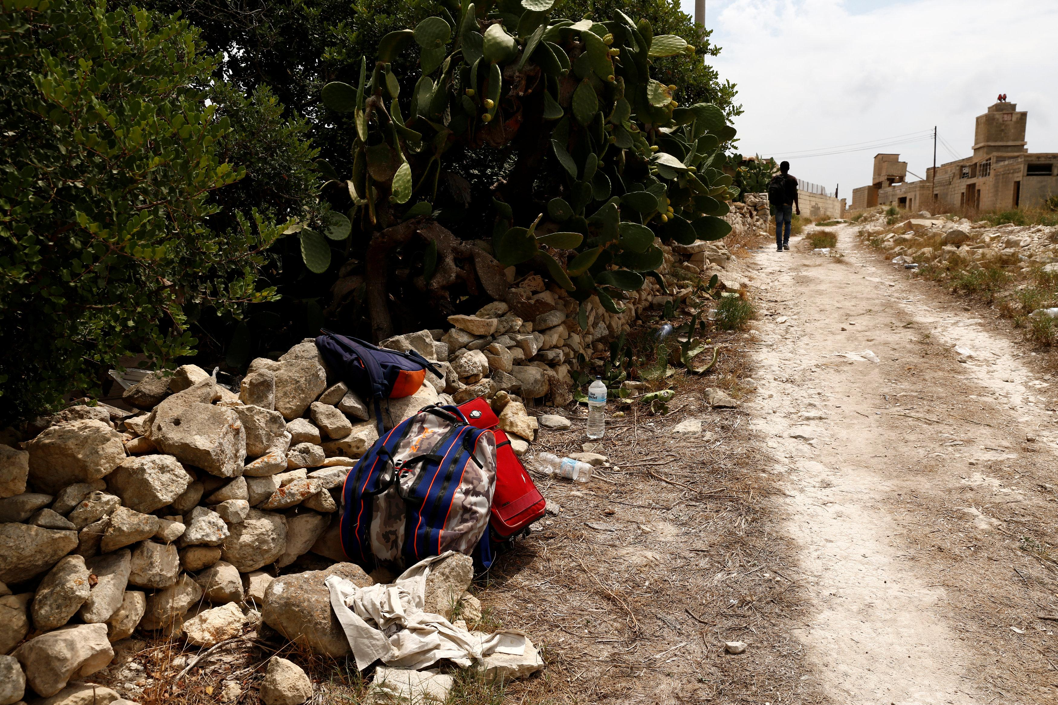 An evicted migrant walks past a farm where police evicted some 110 African migrants who had been living in stalls formerly used by cows, in Qormi, Malta August 13, 2018.  Darrin Zammit Lupi