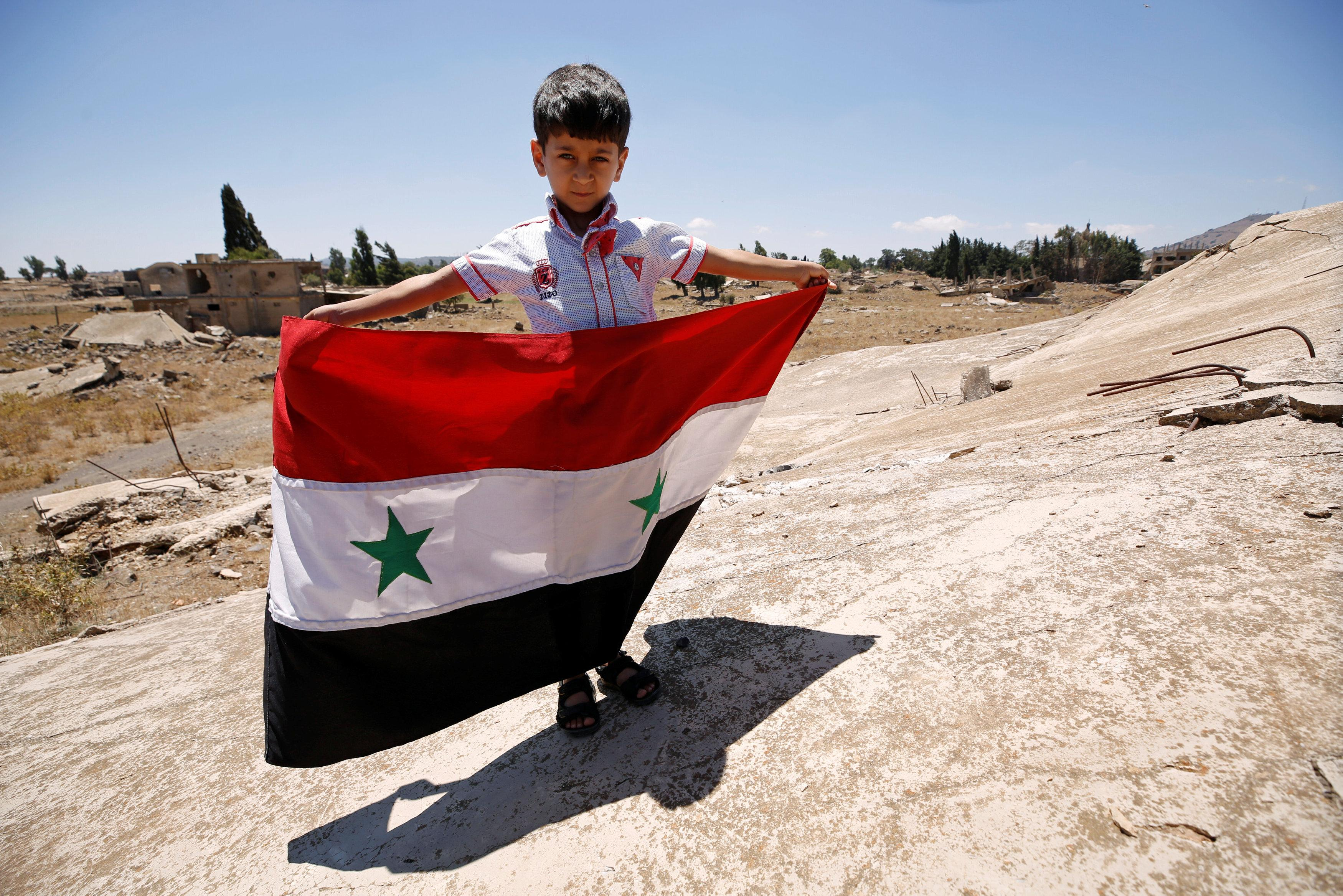 A boy holds the Syrian flag in Quneitra, Syria July 27, 2018. Omar Sanadiki