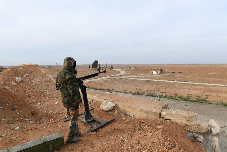 A Syrian Army soldier loyal to Syria's President Bashar al-Assad forces stands next to a military weapon in Idlib, Syria January 21, 2018. SANA/Handout via