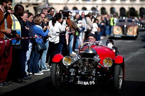 Vintage cars parade through Paris