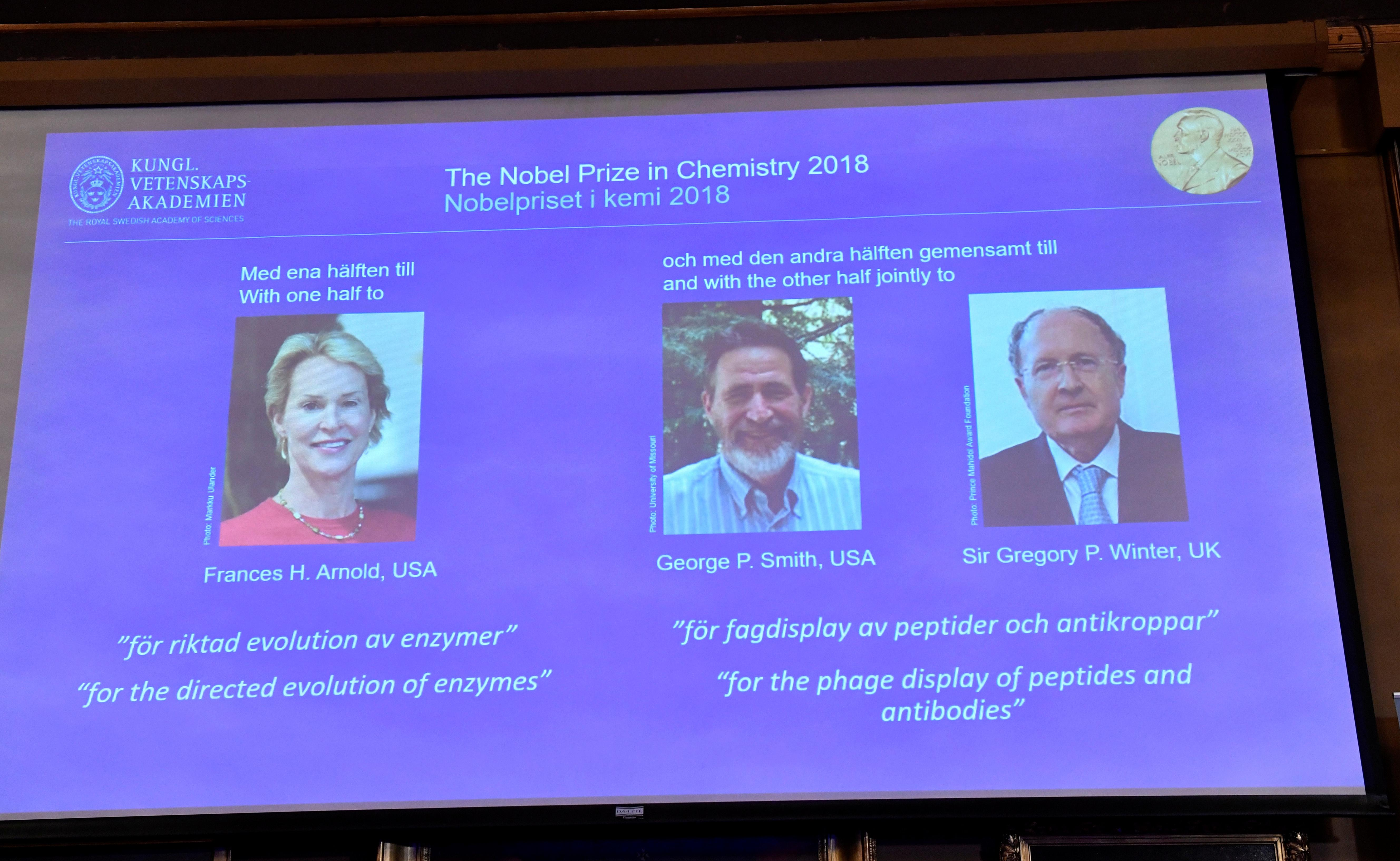 Pictures of the 2018 Nobel Prize laureates for chemistry: Frances H. Arnold of the United States, George P. Smith of the United States and Gregory P. Winter of Britain are displayed on a screen during the announcement at the Royal Swedish Academy of Sciences, in Stockholm, Sweden, October 3, 2018.  Jonas Ekstromer/TT News Agency/via