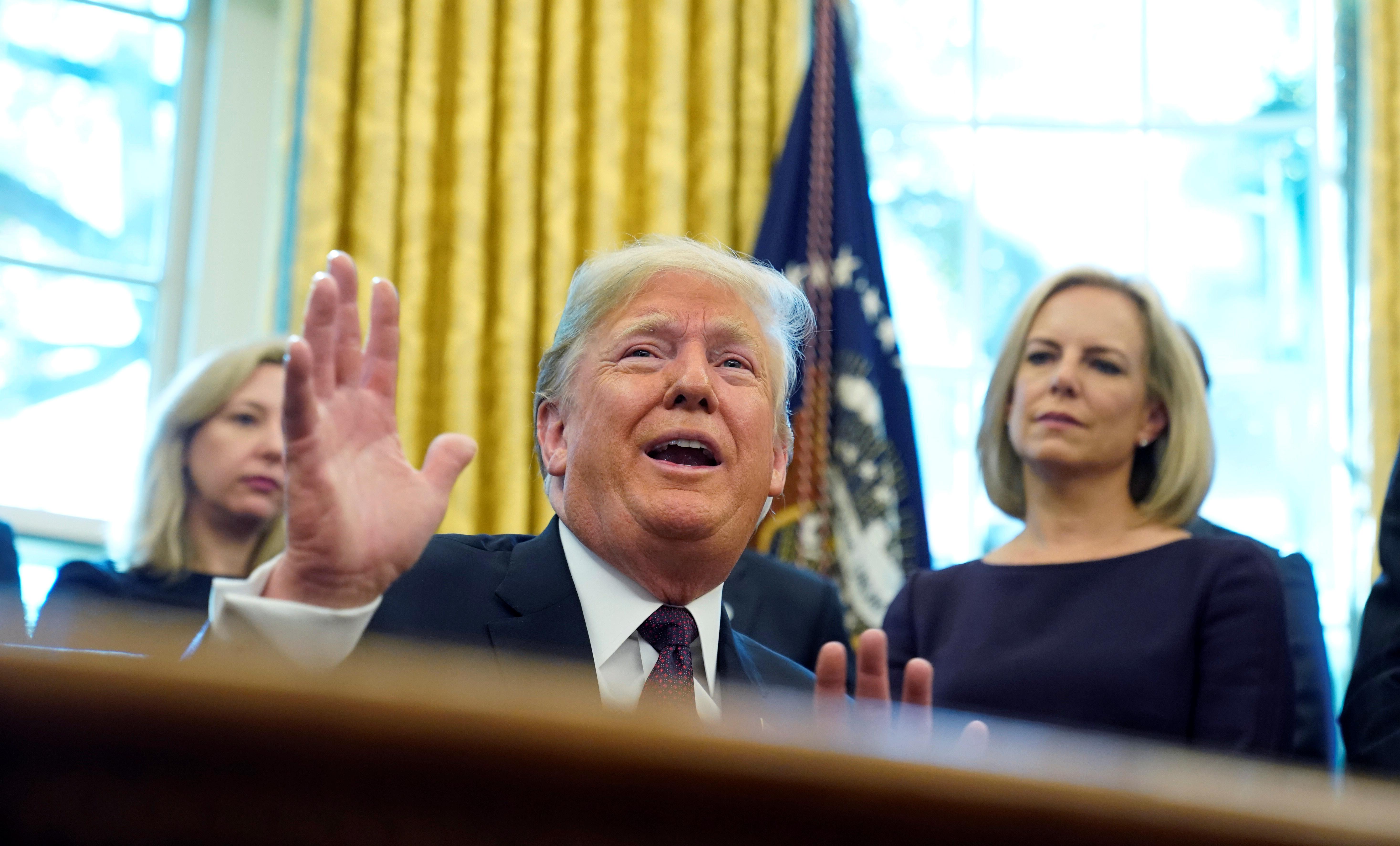 U.S. President Donald Trump talks to reporters as Department of Homeland Security Secretary Kirstjen Nielsen (R) looks on at a signing ceremony for the Cybersecurity and Infrastructure Security Agency Act in the Oval Office of the White House in Washington, U.S. November 16, 2018. Jonathan Ernst
