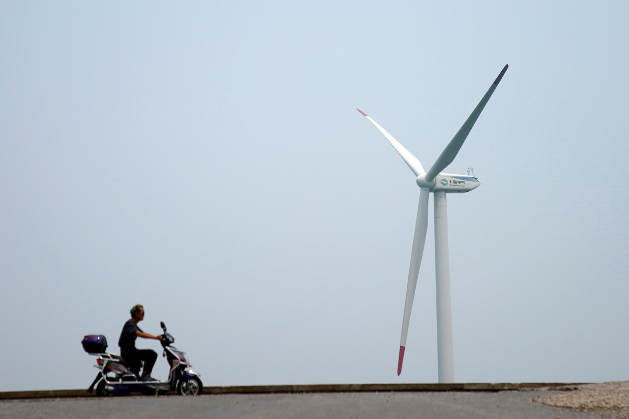 Image result for A man rides an electric scooter past a wind turbine in Shanghai, China August 11, 2017.