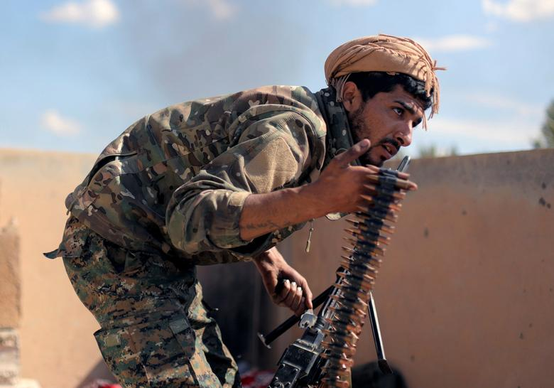 A fighter of Syrian Democratic Forces carries ammunition in Baghouz, Deir Al Zor province, March <span dir=