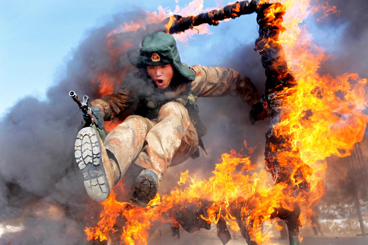 Image result for A frontier soldier from the People's Liberation Army jumps through a ring of fire as part of training in Heihe, Heilongjiang province, March 5, 2014. China Daily via REUTERS