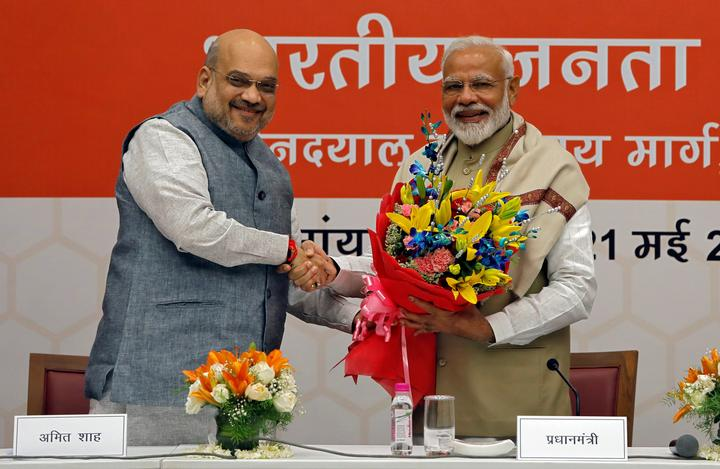 PM Modi shakes hands with BJP President Amit Shah during a thanksgiving...