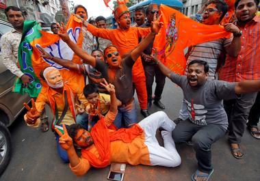 Supporters of Bharatiya Janata Party (BJP) celebrate after learning initial...