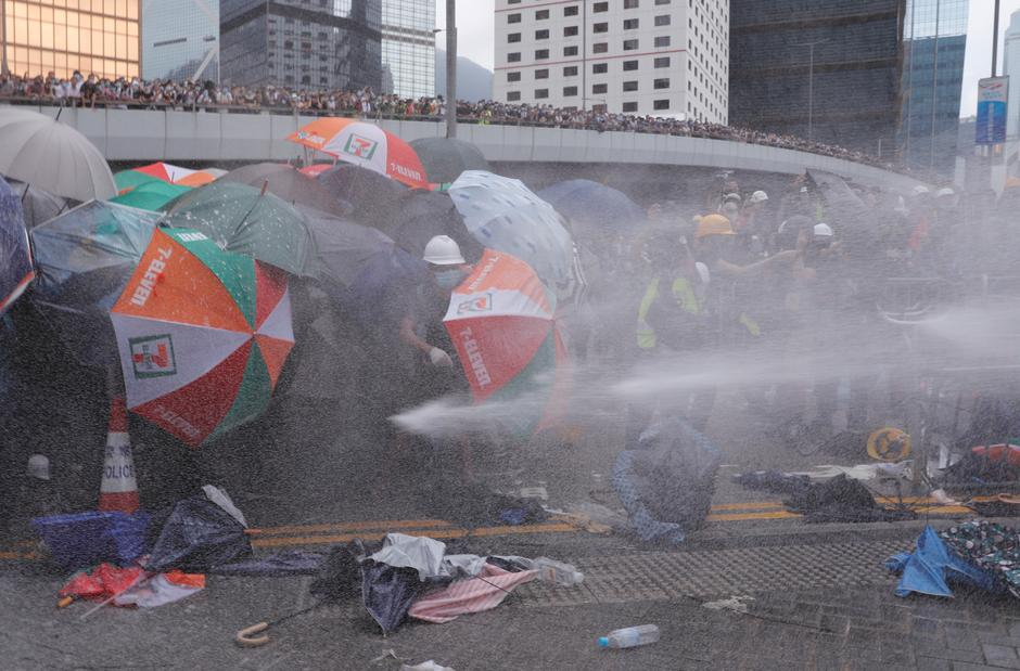 Protesters are hit by police water cannon during a demonstration on June 12. Credit: Tyrone Siu/Reuters