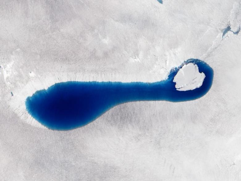Una imagen en color natural muestra un estanque de color zafiro que brota cuando la nieve y el hielo se derriten sobre los glaciares en el sudoeste de Groenlandia en julio de 2010. REUTERS / NASA