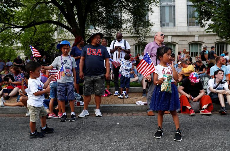 Los niños ondean banderas nacionales mientras las personas participan en las celebraciones del Día de la Independencia en Washington. REUTERS / Eric Thayer