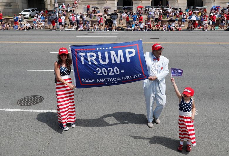 Un hombre y una mujer sostienen una pancarta de la elección de Trump 2020 cuando un niño sostiene una bandera en las celebraciones del Día de la Independencia en Washington. REUTERS / Tom Brenner