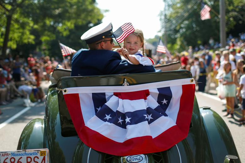 A man and a girl ride in an antique Ford automobile during the annual 4th of July parade in Barnstable Village on Cape Cod, Massachusetts, July 4, 2019. REUTERS/Mike Segar