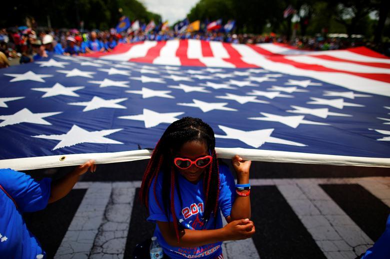 Una niña ayuda a llevar una bandera de los Estados Unidos mientras participa en un desfile durante las celebraciones del Día de la Independencia del 4 de julio en Washington. REUTERS / Carlos Barria