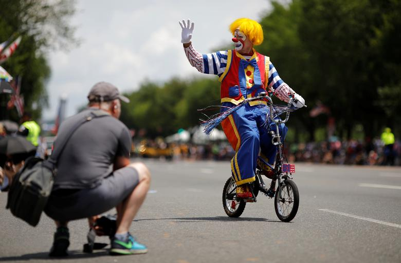 Un payaso pasa en bicicleta mientras participa en un desfile durante las celebraciones del Día de la Independencia del 4 de julio en Washington. REUTERS / Carlos Barria