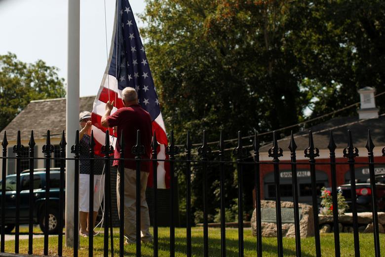 La gente levanta una bandera estadounidense en un asta de bandera en Barnstable Village en Cape Cod, Massachusetts. REUTERS / Mike Segar
