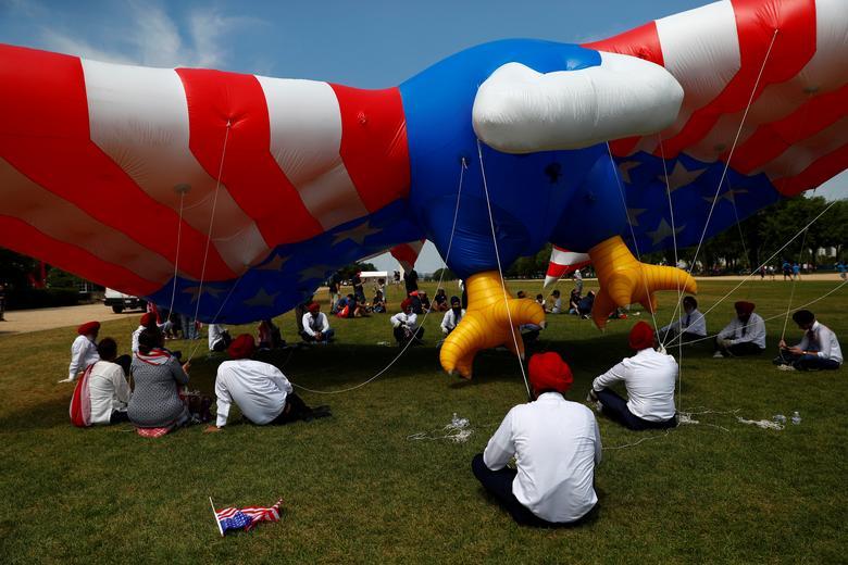 Los participantes se sientan bajo un gigantesco águila inflable con la bandera de Estados Unidos durante las celebraciones del Día de la Independencia en Washington. REUTERS / Eric Thayer