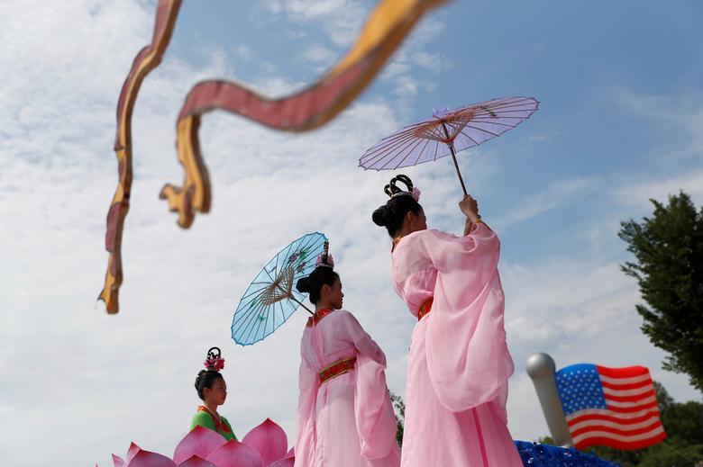 Las mujeres tienen sombrillas cuando participan en las celebraciones del Día de la Independencia en Washington. REUTERS / Eric Thayer