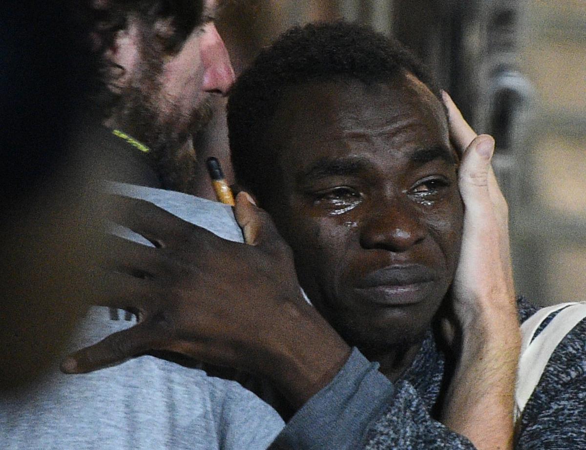 Migrante gaan van die Open-arms-reddingsskip af op die Italiaanse eiland Lampedusa