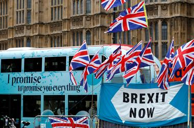 FILE PHOTO: A passenger bus passes a pro-Brexit demonstration in...