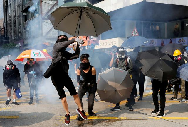 An anti-government demonstrator throws back a tear gas canister during a protest march in Hong Kong, China, October 20, 2019. REUTERS/Kim Kyung-Hoon