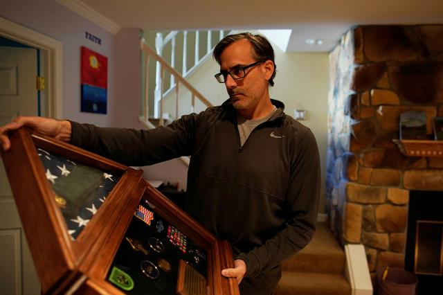 Mark Giaconia, who served for 20 years in the U.S. Army, of which 15 years in the U.S. Special Forces and was embedded with the Kurds in Iraq, shows his medals at his house in Herndon, Virginia, U.S., October 19, 2019. Picture taken October 19, 2019.  REUTERS/Carlos Jasso