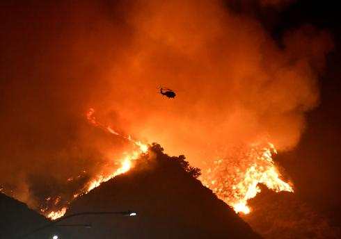 Fast-moving California wildfires force thousands to flee