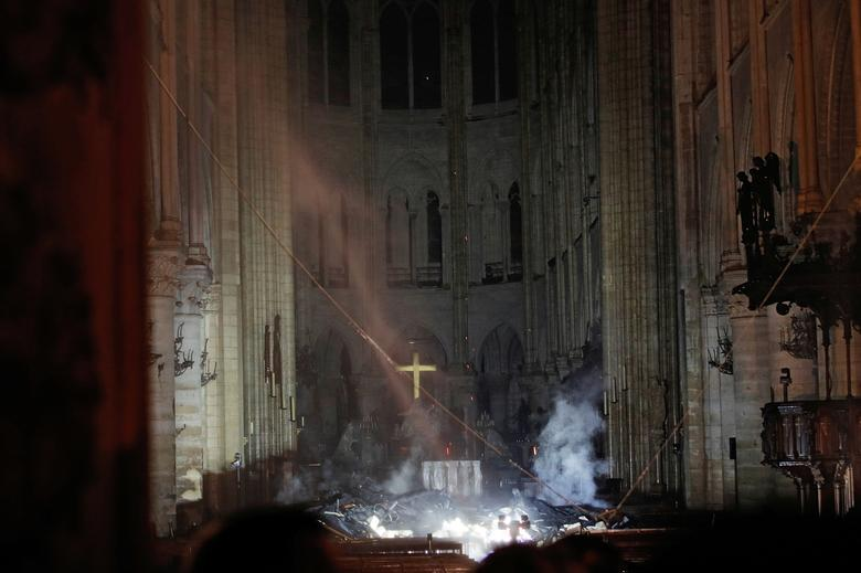 Smoke rises around the altar in front of the cross inside the Notre Dame Cathedral as a fire burns in Paris, France, April 16, 2019. REUTERS/Philippe Wojazer/Pool