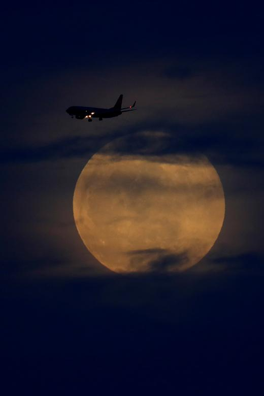 A full moon rises between clouds as a landing commercial jet approaches the airport before the start of a total lunar eclipse that is being called a 'Super Blood Wolf Moon' in San Diego, California, January 20, 2019. REUTERS/Mike Blake