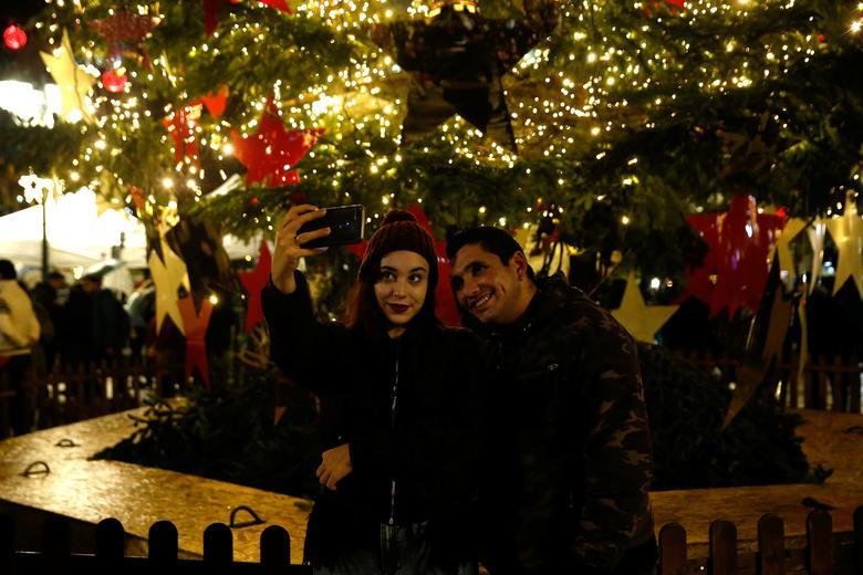Una mujer se toma una selfie durante una ceremonia de iluminación del árbol de Navidad en la plaza Syntagma en Atenas, Grecia, 10 de diciembre de 2019. REUTERS / Constantina Peppa