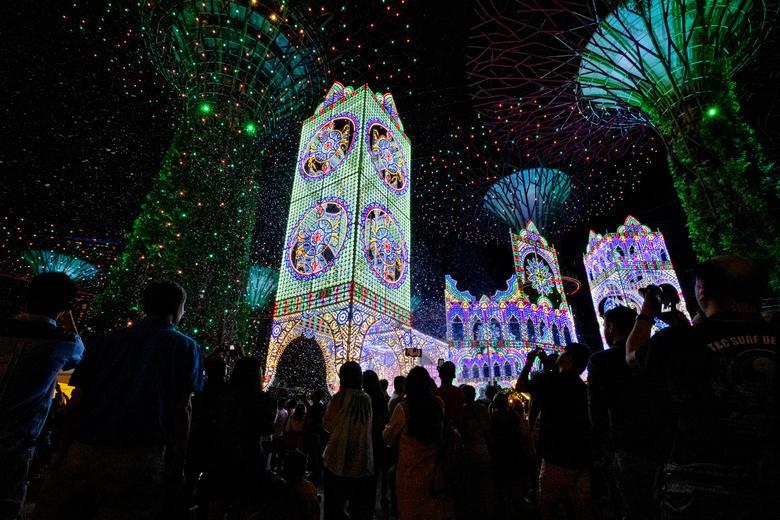 La gente ve esculturas de luz luminarie en medio de espuma de nieve durante el evento Christmas Wonderland en Gardens by the Bay en Singapur, 15 de diciembre de 2019. REUTERS / Loriene Perera