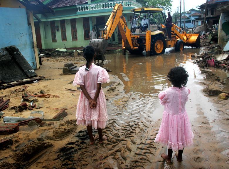 Dos jóvenes musulmanas observan cómo una excavadora despeja un camino en una calle destruida por el tsunami en la ciudad de Kalumnai, en la costa este de Sri Lanka, el 4 de enero de 2005. REUTERS / Kieran Doherty