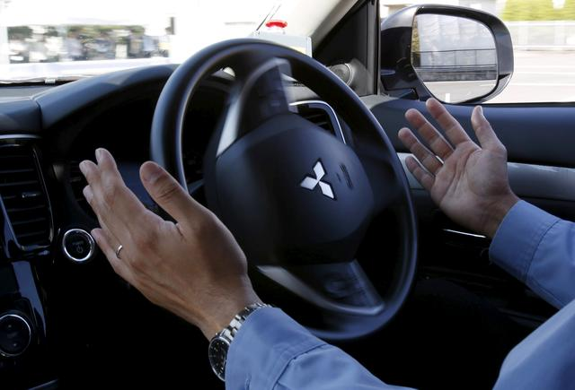 FILE PHOTO: A staff member of Mitsubishi Electric drives its self-driving concept car ''EMIRAI3 xAUTO'' using the hands-free function during a media preview in Kamakura, south of Tokyo, Japan, October 14, 2015.  REUTERS/Yuya Shino/File Photo