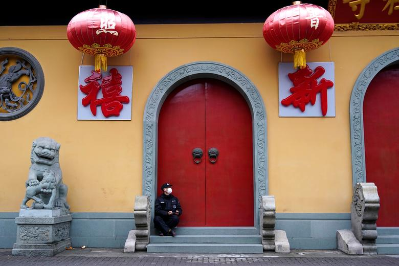 A security guard sits at the entrance of a closed temple in Shanghai, China January 24, 2020. REUTERS/Aly Song