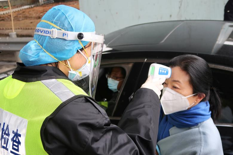 A security officer in a protective mask checks the temperature of a passenger following the outbreak of a new coronavirus, at an expressway toll station on the eve of the Chinese Lunar New Year celebrations, in Xianning, a city bordering Wuhan to the north, Hubei province, China January 24, 2020. China shut part of the Great Wall and suspended public transport in 10 cities, stranding millions of people at the start of the Lunar New Year holiday on Friday as authorities rush to contain a virus that has killed 26 people and infected more than 800. REUTERS/Martin Pollard