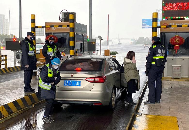 Police officers wearing masks check the trunk of a car for smuggled wild animals at an expressway toll station following the outbreak of a new coronavirus, on the eve of the Chinese Lunar New Year celebrations, outside Wuhan, Hubei province, China January 24, 2020. REUTERS/David Stanway