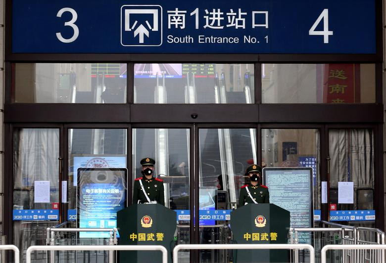 Chinese paramilitary officers wearing masks stand guard at an entrance of the closed Hankou Railway Station after the city was locked down following the outbreak of a new coronavirus in Wuhan, Hubei province, China January 23, 2020. China Daily via REUTERS