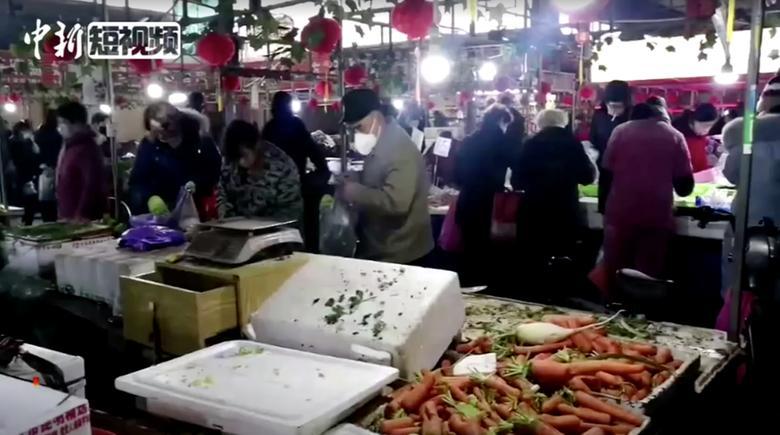 La gente usa máscaras en un mercado en Wuhan, provincia de Hubei, el 23 de enero. China News Service / vía REUTERS TV