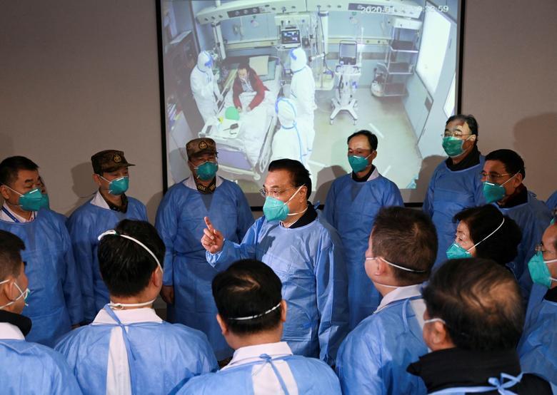 El primer ministro chino, Li Keqiang, con una máscara y un traje de protección, habla con los trabajadores médicos mientras visita el hospital Jinyintan donde se trata a los pacientes del nuevo coronavirus, en Wuhan, provincia de Hubei, China, el 27 de enero de 2020. La ciudad de 11 millones de personas está En el cierre virtual y gran parte de Hubei, hogar de casi 60 millones de personas, se encuentra bajo algún tipo de restricción de viaje. cnsphoto vía REUTERS