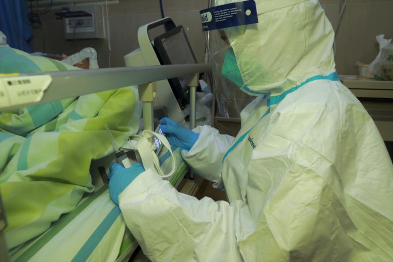 El personal médico atiende a un paciente con neumonía causada por el nuevo coronavirus en el Hospital Zhongnan de la Universidad de Wuhan, en Wuhan, provincia de Hubei, China, el 22 de enero. Cnsphoto vía REUTERS