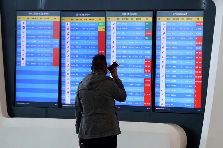 Un hombre se para frente a una pantalla que muestra que se cancelaron varios vuelos de salida después de que la ciudad fuera bloqueada, en un aeropuerto en Wuhan, provincia de Hubei, China, el 23 de enero. Fotografia vía REUTERS