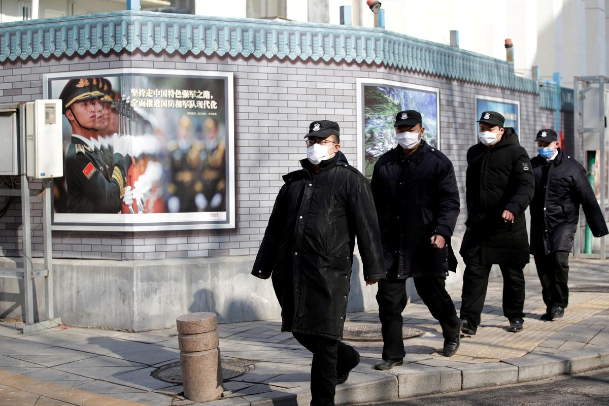 FILE PHOTO: Security personnel wearing masks walk along the Financial Street in central Beijing, China, as the country is hit by an outbreak of the new coronavirus, February 3, 2020. REUTERS/Jason Lee