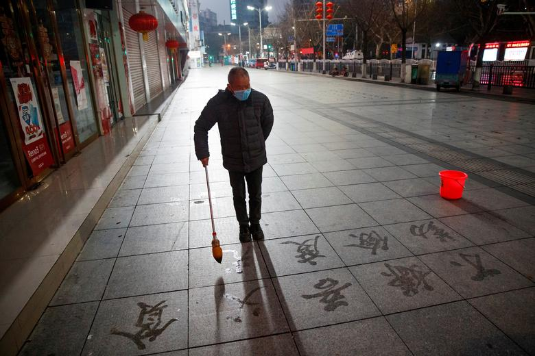 A man wears a face mask as he practices calligraphy on the  pavement in Jiujiang, Jiangxi province, China, February 3.    REUTERS/Thomas Peter