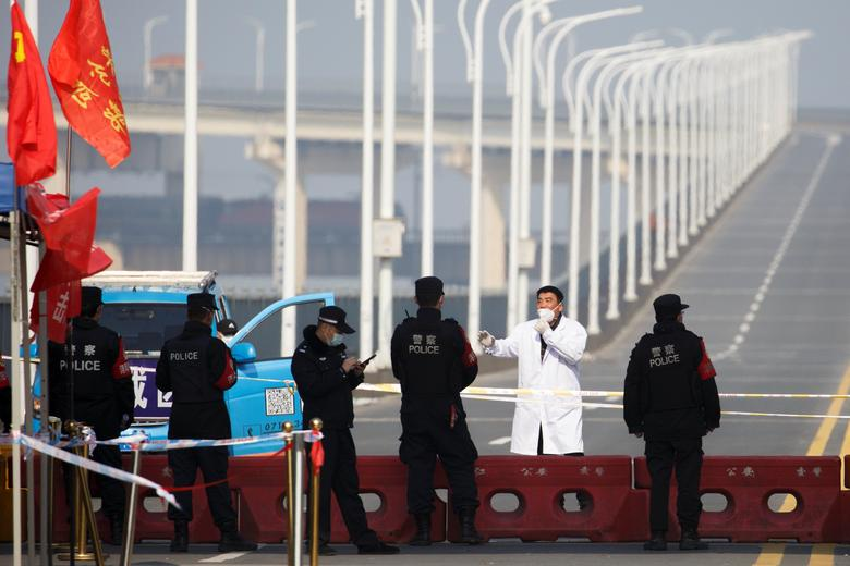 A man who arrived from Hubei province talks with police at a checkpoint at the Jiujiang Yangtze River Bridge in Jiujiang, Jiangxi province, China, February 4. REUTERS/Thomas Peter