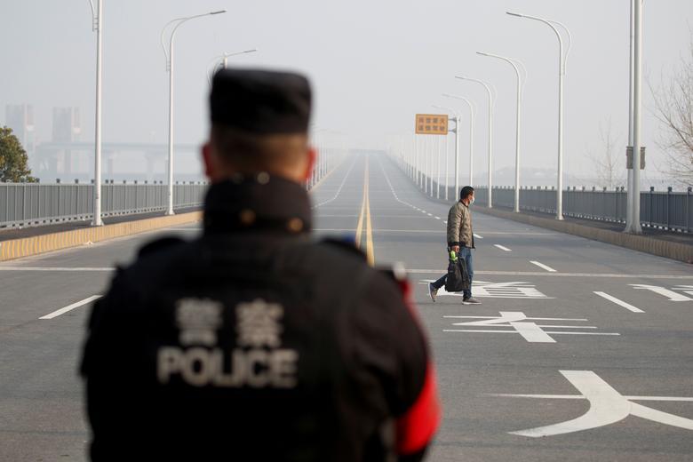 A man arriving from Hubei province approaches a checkpoint at the Jiujiang Yangtze River Bridge in Jiujiang, Jiangxi province, January 31.     REUTERS/Thomas Peter