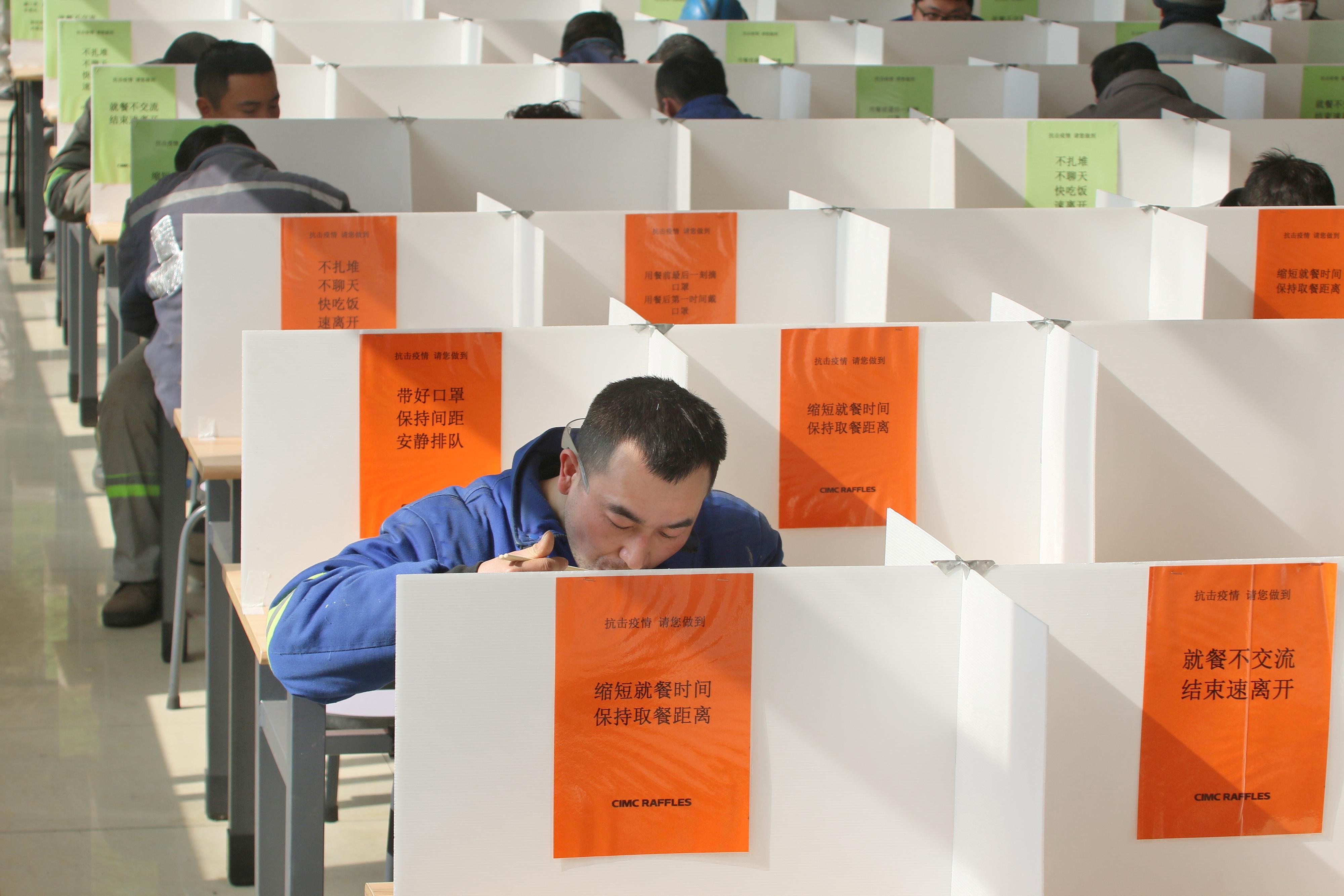 Déjeuners et masques en solo: les Chinois retournent au travail aux prises avec le coronavirus