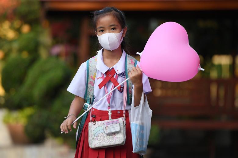Una niña llega a una escuela con una máscara protectora el día de San Valentín en Ayutthaya, en las afueras de Bangkok, Tailandia.  REUTERS / Chalinee Thirasupa