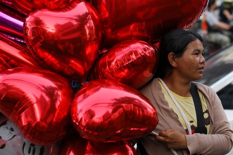 Una mujer vende globos para celebrar el Día de San Valentín en Bangkok, Tailandia.  REUTERS / Jorge Silva