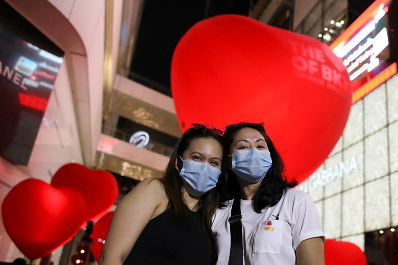 Las mujeres que llevan máscaras protectoras posan frente a los corazones que celebran el Día de San Valentín frente al centro comercial en Bangkok, Tailandia.  REUTERS / Jorge Silva