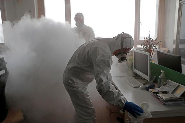 FILE PHOTO: Workers with sanitising equipment disinfect an office following an outbreak of coronavirus in the country, in Shanghai, China February 12, 2020. cnsphoto via REUTERS/File Photo