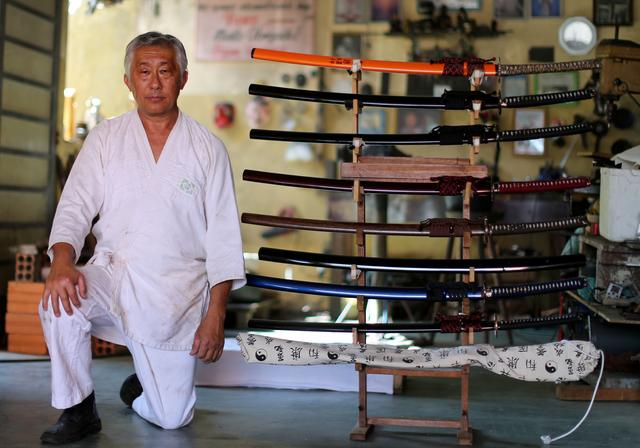 Samurai Edson Suemitsu poses for pictures next to katana swords at his home in Curitiba, Brazil February 17, 2020. Picture taken February 17, 2020.  REUTERS/Rodolfo Buhrer